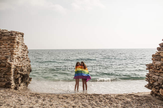 Back view of lesbian couple standing on beach with colorful flag of LGBT movement during summer vacation — Stock Photo