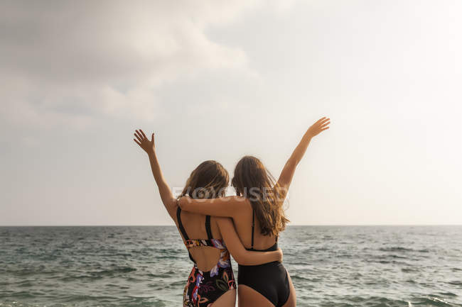 Back view of young women in swimsuits standing by sea, embracing with raising hands — Stock Photo