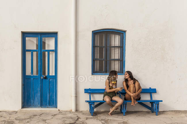 Happy young women in tops and shorts sitting on bench and using cellphone — Stock Photo