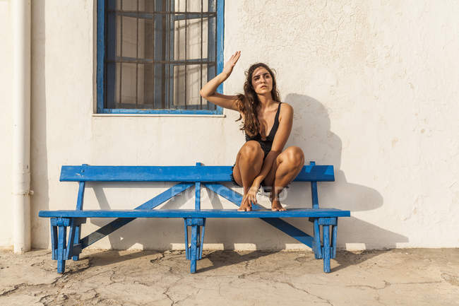 Mulher bonita magro olhando para longe, agachando-se no banco de madeira por construção de pedra no dia ensolarado — Fotografia de Stock
