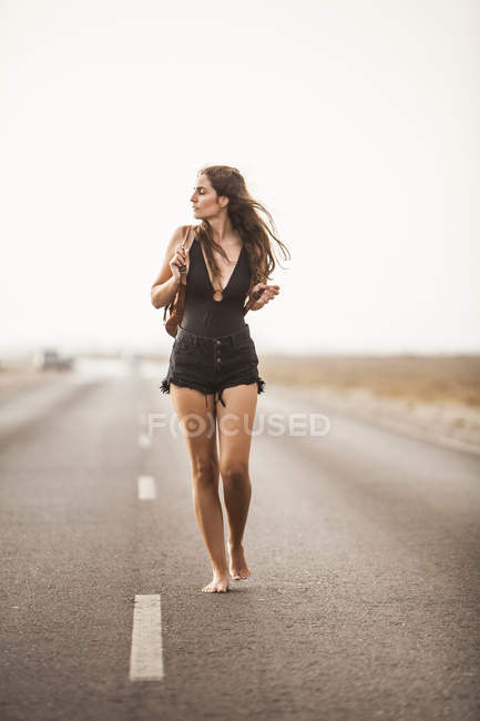 Attractive young barefoot woman walking on empty road, holding backpack and looking away — Stock Photo