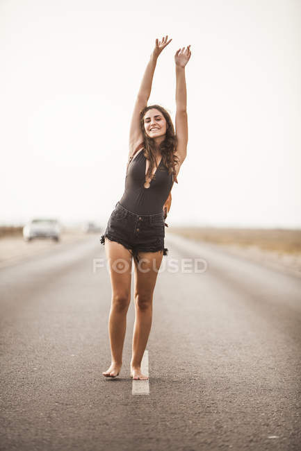 Attractive young barefoot woman smiling and walking on empty road with backpack, raising hands and looking at camera — Stock Photo