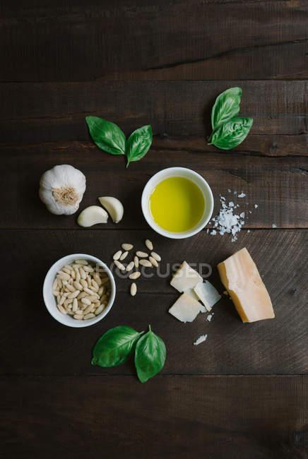 Ingredientes para pasta de pesto dispuestos en la mesa de madera, vista superior. - foto de stock