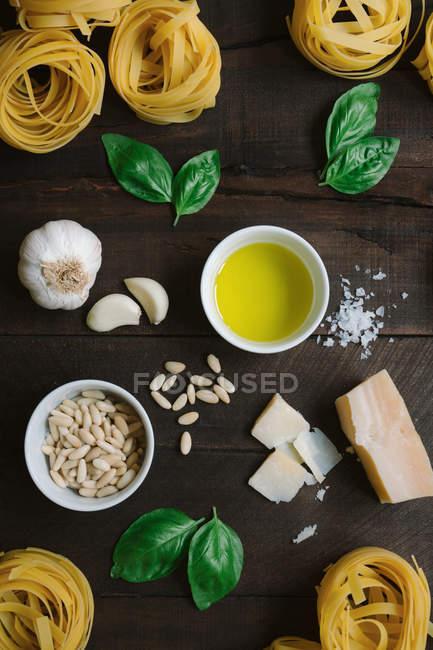 Vista superior de hierbas frescas y queso con aceite y pasta de tagliatelle dispuestas en la mesa rústica de madera. - foto de stock