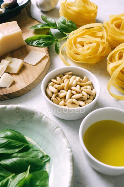 Сосні горіхи в тарілці і інгредієнти для соусу пепто з талателлю на столі. — стокове фото