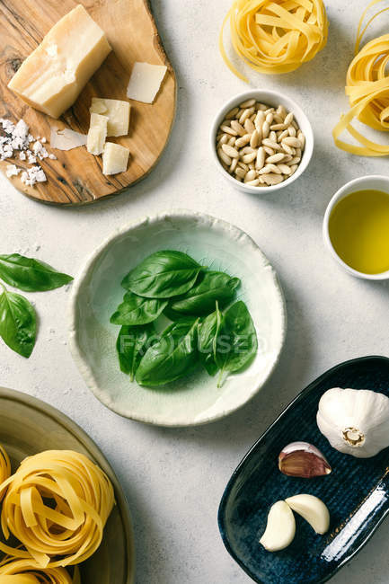Basil leaves and ingredients for pesto sauce on plates on table — Stock Photo