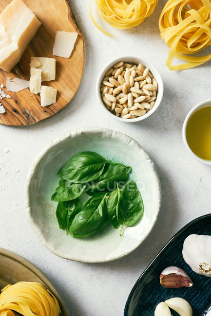 Frische grüne Basilikumblätter auf Tellern neben Pinienkernen und Parmesan auf weißem Küchentisch — Stockfoto