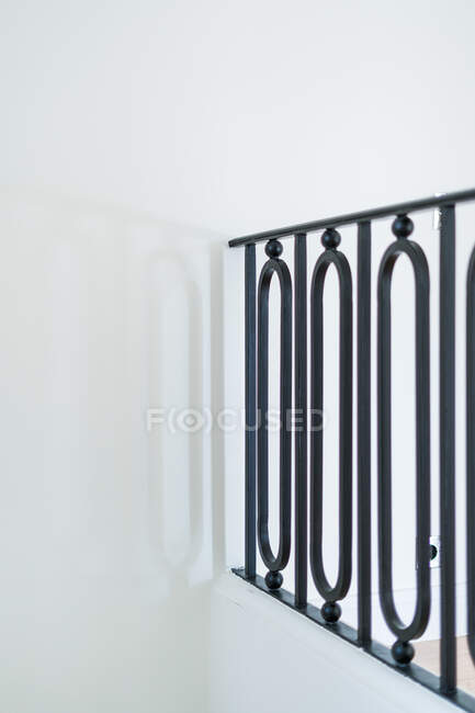 Forged decorative black railing in stylish light minimalist interior on white background — стоковое фото