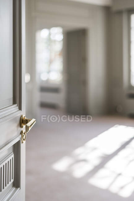 Open white door with golden handle in light minimalist interior on blurred background — Stock Photo
