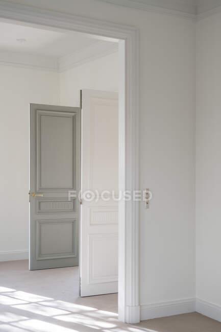 Porta aperta a battente bicolore con maniglia moderna in bianco interno minimalista — Foto stock