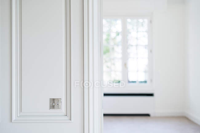 Metal switch on white wall in room with trendy minimalist interior — Stock Photo