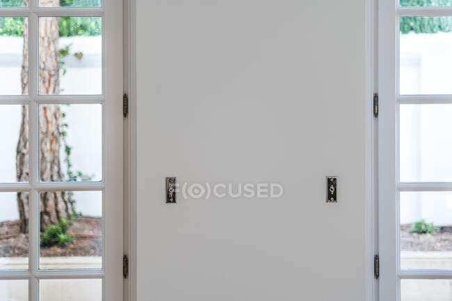 White wall with steel latches and closed white entrance door in house with light interior — Stock Photo