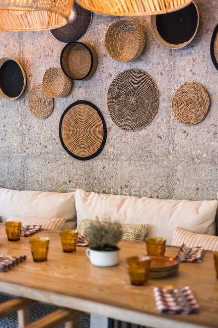 Authentic wicker lampshades with warm light hanging over served table in empty outside restaurant — Stock Photo