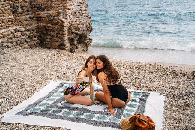 Side view of stylish young women in swimwear relaxing on seashore and taking picture by smartphone — Stock Photo