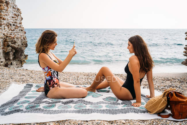 Side view of stylish young women in swimwear relaxing on seashore and taking picture by smartphone — Photo de stock
