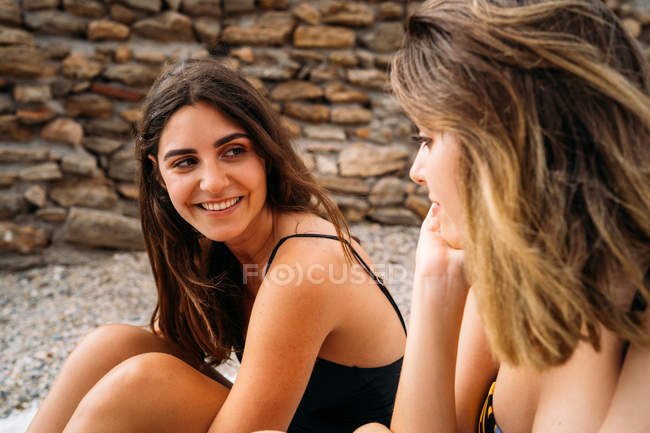 Happy young women in swimwear relaxing, sitting on blanket and looking at each other on seashore — Stock Photo