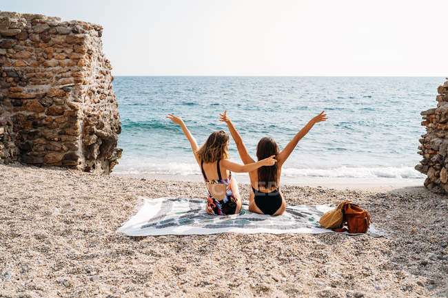 Back view of women in swimwear relaxing on blanket on seashore and raising hands — Stock Photo