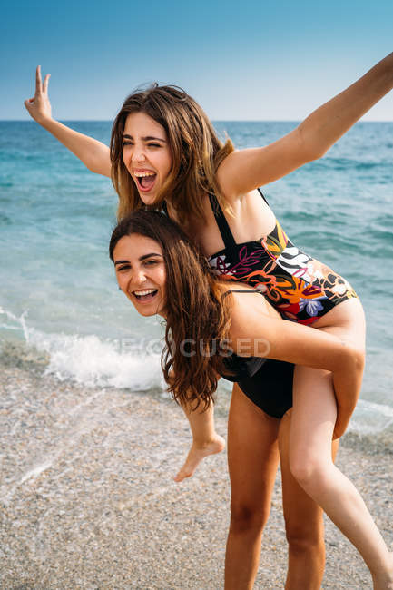 Happy attractive woman giving piggyback to young girlfriend with outstretched hands — Stock Photo