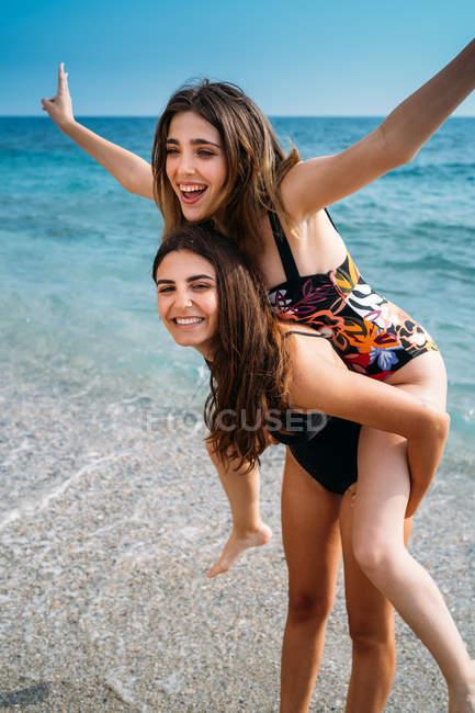 Счастливая привлекательная женщина, подарившая хвост молодой девушке с протянутыми руками — стоковое фото