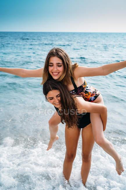 Feliz mujer atractiva dando la espalda a la joven novia con las manos extendidas. - foto de stock