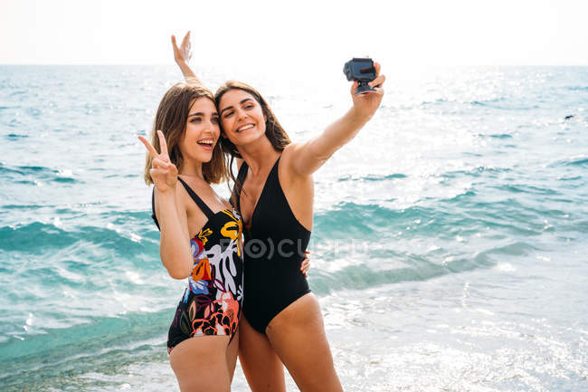 Cheerful women in trendy swimsuits taking picture by camera, hugging and showing victory sign — Stock Photo