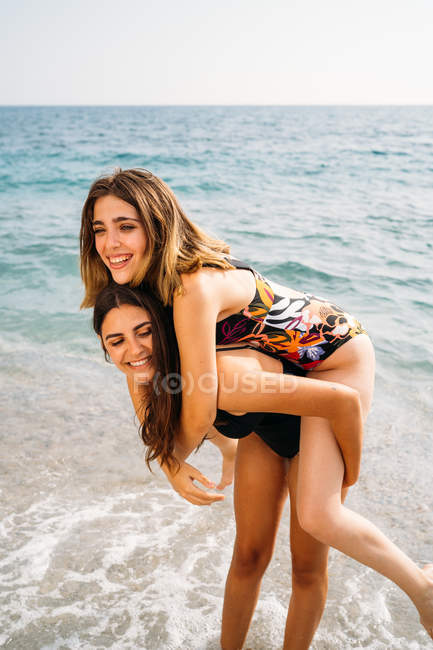 Happy attractive woman giving piggyback to young girlfriend — Stock Photo