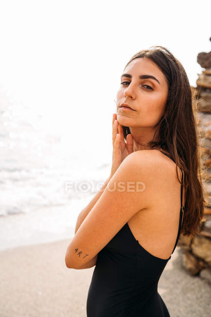 Side view of attractive pensive woman in black swimwear relaxing on seashore by stone wall and looking at camera — Stock Photo