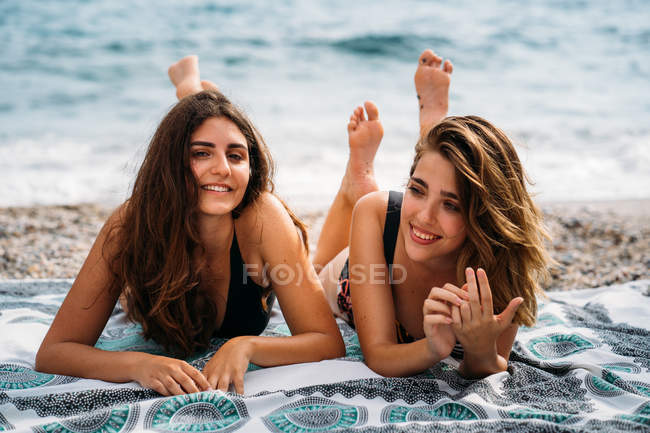 Happy young women in swimwear relaxing on blanket with raised feet, smiling and looking at camera on seashore — Stock Photo