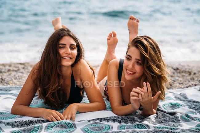 Счастливые молодые женщины в купальниках расслабляются на одеяле с поднятыми ногами, улыбаются и смотрят в камеру на берегу моря — стоковое фото