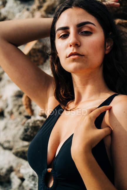 Приваблива задумлива жінка в чорному купальнику відпочиває на березі, спираючись на кам'яну стіну і дивиться на камеру — стокове фото