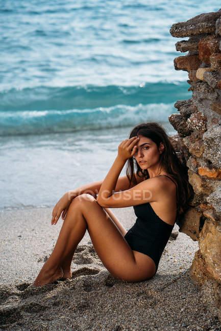 Вид сбоку привлекательной застенчивой женщины в черном купальнике, расслабляющейся на берегу моря и смотрящей в камеру — стоковое фото