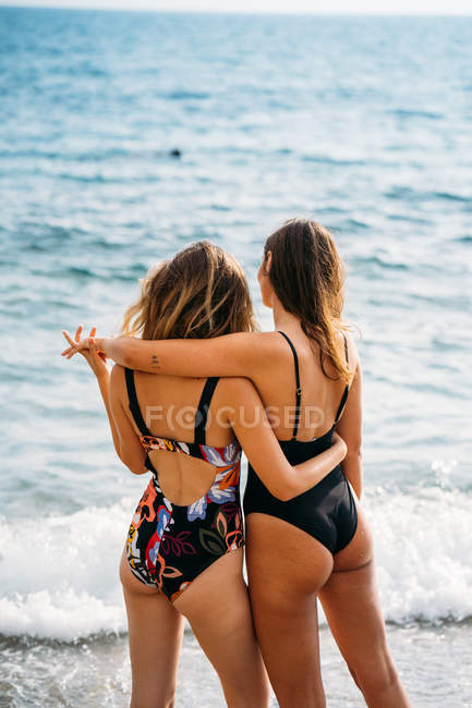Back view of young women in swimsuits standing by sea, embracing and contemplating seascape on sunny day — Stock Photo