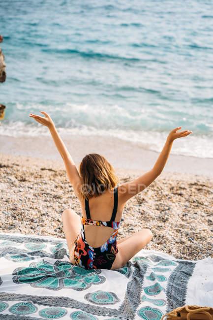 Vista posteriore della femmina in costume da bagno colorato e cuffie gialle godendo musica alzando le mani rilassante sulla spiaggia — Foto stock
