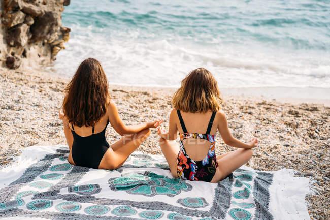 Обратный вид женщин в купальниках, сидящих на одеяле в позе лотоса, практикующих йогу по каменному строительству — стоковое фото