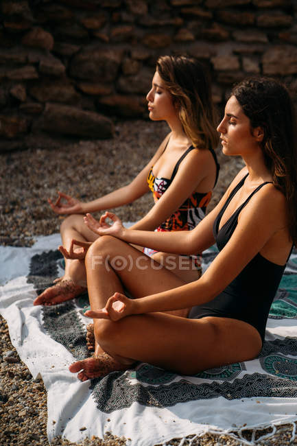 Side view of attractive women in swimsuits sitting on blanket in lotus position while practicing yoga by stone construction — Stock Photo