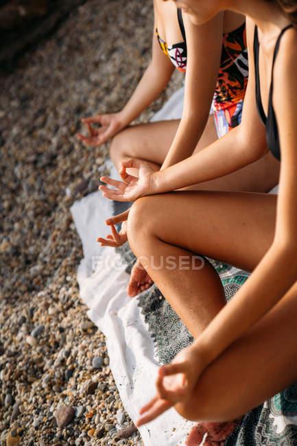 Обрезанное изображение женщин в купальниках, сидящих на одеяле в позе лотоса, практикующих йогу по каменному строительству — стоковое фото