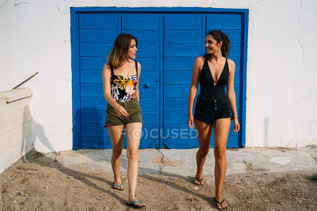 Cheerful young women in swimsuits and shorts walking, smiling and looking at each other on sunny day — Stock Photo