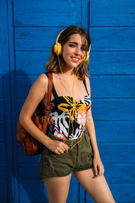 Jovem mulher positiva com mochila em pé junto à parede de madeira, ouvindo música sorrindo e olhando para a câmera — Fotografia de Stock