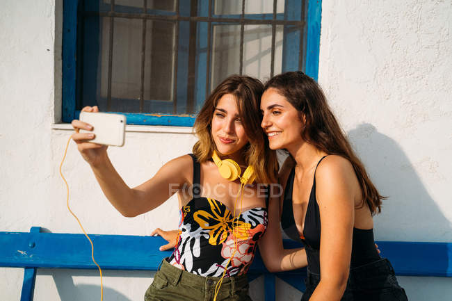 Happy young women in tops and shorts sitting on bench, embracing and taking selfie on smartphone — Stock Photo