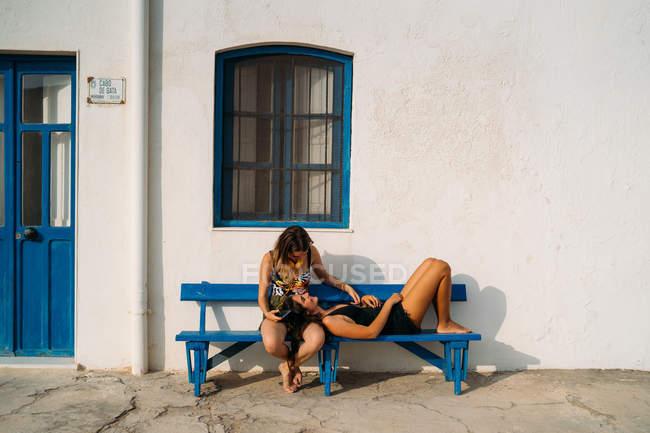 Junges Mädchen sitzt mit Smartphone und Kopfhörer auf Bank und lächelt fröhliche Frau an, die tagsüber auf Knien liegt — Stockfoto