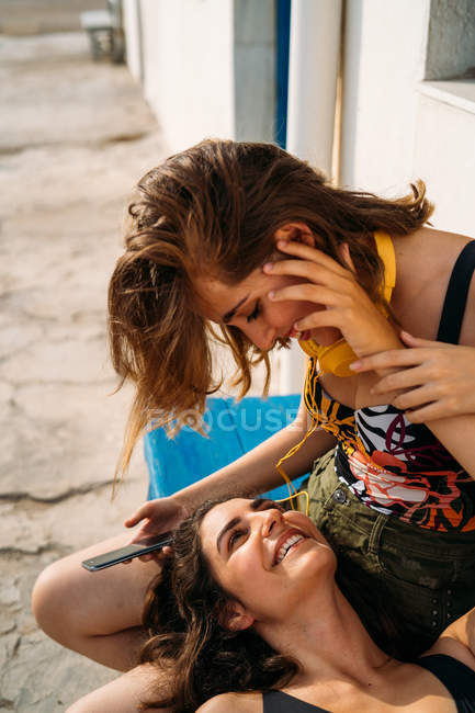 Young girl sitting on bench with smartphone and headphones, smiling at cheerful woman lying on knees on daytime — Stock Photo