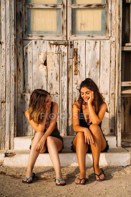 Casal feminino afetuoso sentado perto de galpão de madeira velho, falando e sorrindo no dia ensolarado — Fotografia de Stock