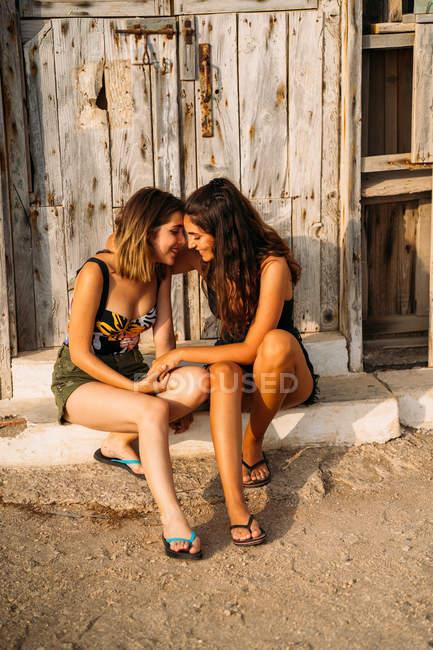 Casal feminino afetuoso sentado por velho galpão de madeira, de mãos dadas e tocando com as testas — Fotografia de Stock