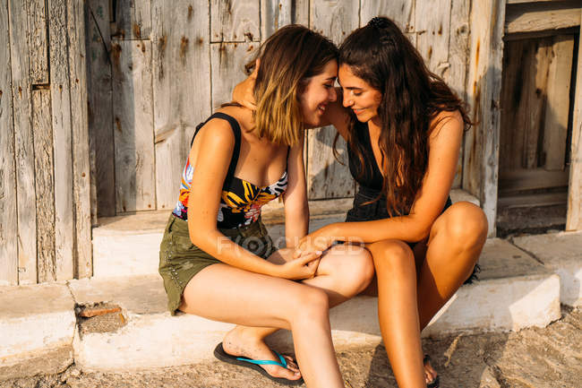 Affectionate female couple sitting by old wooden shed, holding hands and touching with foreheads — Stock Photo
