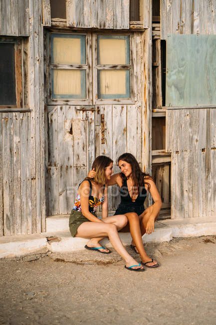 Couple féminin affectueux assis près d'un vieux hangar en bois, s'embrassant et se regardant — Photo de stock