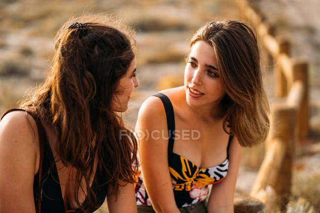 Women with backpack relaxing on wooden fence, chatting and looking at each other on blurred nature background — Stock Photo