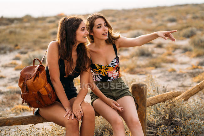 Women with backpack relaxing on wooden fence, pointing with forefinger and looking away on blurred nature background — Stock Photo