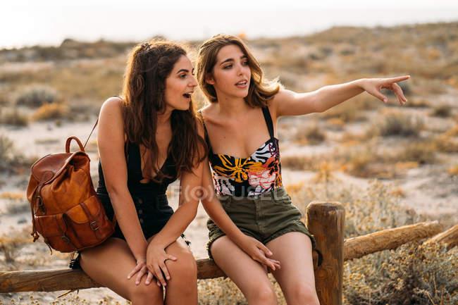 Женщины с рюкзаком отдыхают на деревянном заборе, указывая указательным пальцем и отводя взгляд на размытый природный фон — стоковое фото