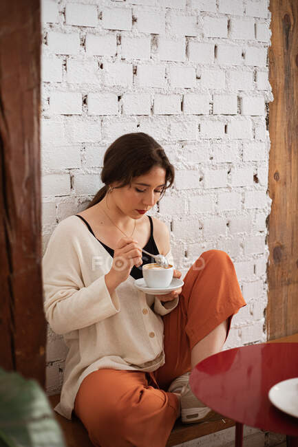 Peaceful woman drinking coffee while resting at home — Stock Photo