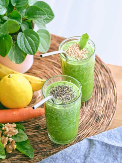 Set de ingredientes para batidos saludables y vasos con bebida verde - foto de stock